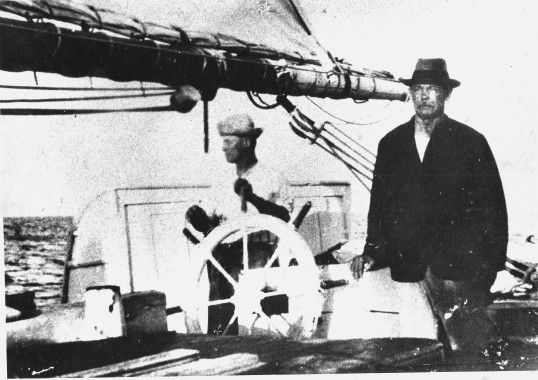 Capt. John Clarence at the wheel of the 'Maisie Hassell' and his brother standing Capt. William Benjamin Hassell